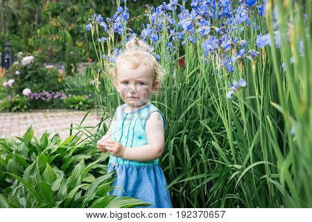 Sad little girl is standing in a flower bed.