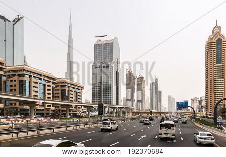 DUBAI, UAE - CIRCA AUGUST 2016:Multi Lane Highway Through Modern Downtown Dubai Lined with Skyscrapers with View of Burj Khalifa in Background on Hazy Overcast Day, Dubai, United Arab Emirates