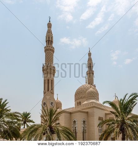 DUBAI, UAE - CIRCA AUGUST 2016:Architectural Exterior of Fatimid Style Jumeirah Mosque Surrounded by Palm Trees in Dubai City, United Arab Emirates on Sunny Day with Blue Sky