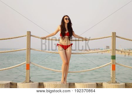 Young female with dark brown hair standing near rope bridge at Dubai beach. Slim brunette in red bikini relaxing and having fun at the sea