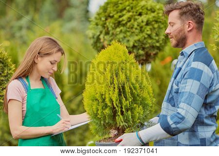 Young gardener woman standing and writing in documents while man doing horticulture job in the garden.