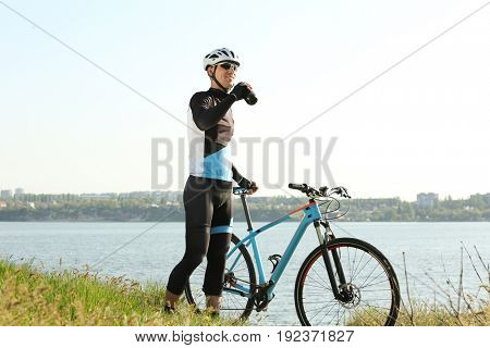 Sporty cyclist drinking beverage while standing near river with bicycle
