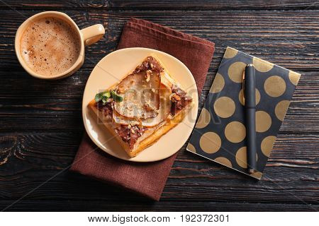 Plate with delicious pastry, stationery and cup of coffee on wooden table