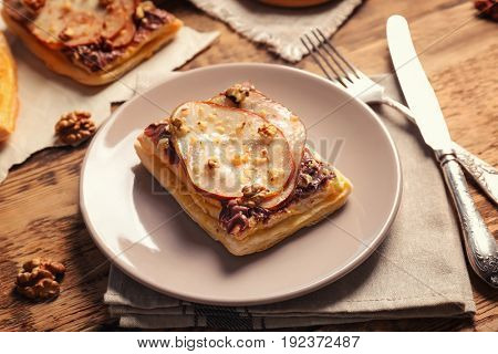 Plate with delicious pastry and flatware on wooden table