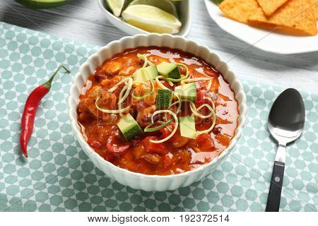 Bowl with delicious chili turkey on table