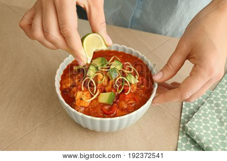 Woman squeezing lime juice into bowl with chili turkey, closeup