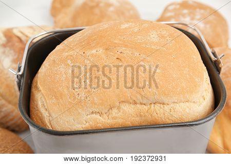 Freshly baked loaf in bread machine pan, closeup