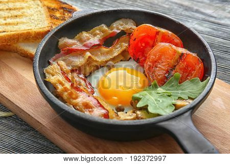 Frying pan with tasty egg, bacon and tomatoes on table