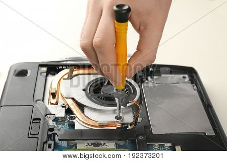 Dismantling laptop with screwdriver, closeup view. Concept of computer repair