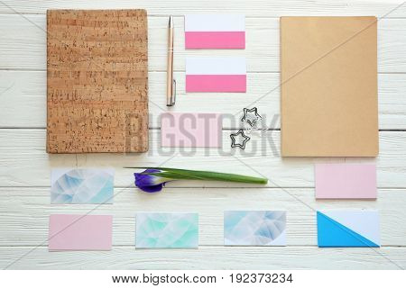 Beautiful composition of business cards, stationery and flower on wooden background