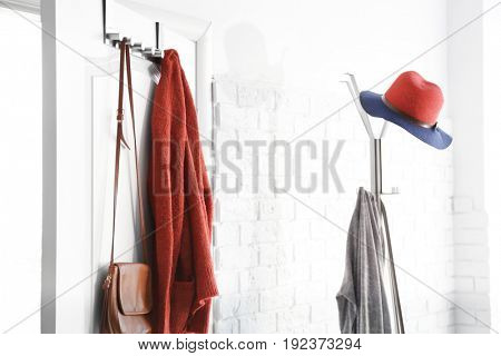 Hanging clothes on door in modern hall interior