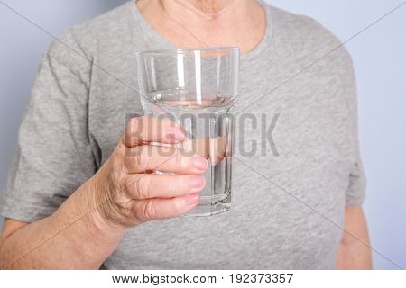 Elderly woman holding glass of water on grey background. Concept of retirement