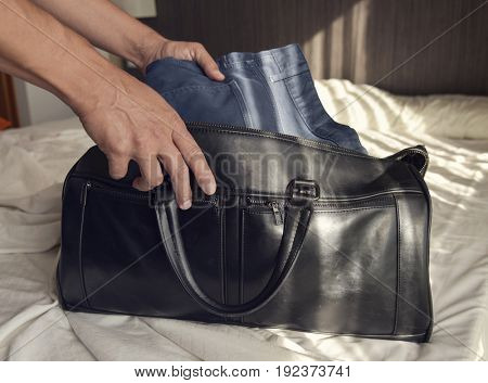 closeup of a young caucasian man putting clothes in a travel bag or putting them off, on the bed