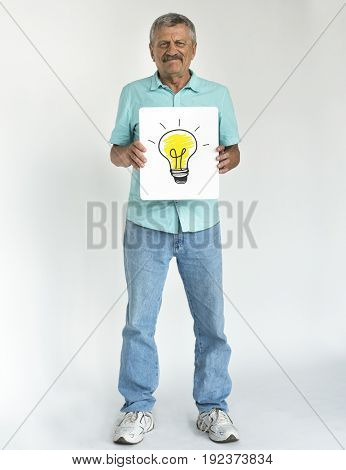 Senior man holding placard lightbulb
