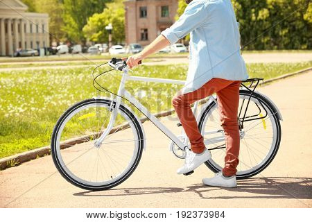 Sporty young man with bicycle outdoors