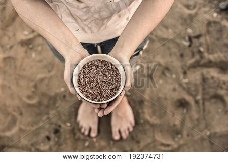 Poverty concept. Poor woman holding bowl with buckwheat, outdoors