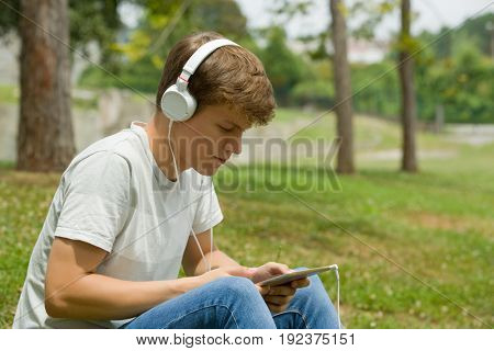 young man relaxing with a tablet pc listening music with headphones at the park, outdoor