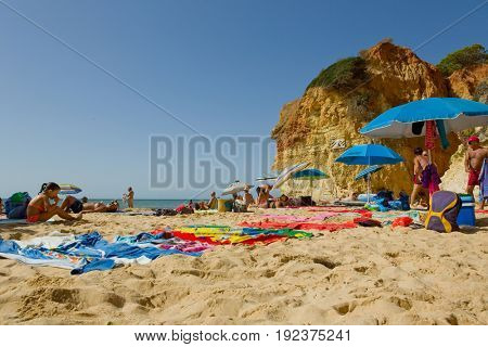 ALBUFEIRA, PORTUGAL - AUGUST 25, 2016: People at the famous beach of Olhos de Agua in Albufeira. This beach is a part of famous tourist region of Algarve.