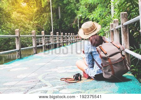 Happy asian backpacker sitting on beautiful walk way with nature Summer travel concept