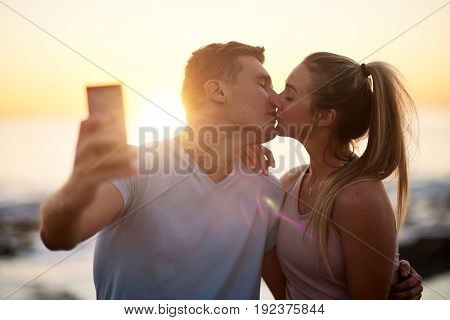 Romantic couple on date take a selfie with the sunset, kissing by the ocean