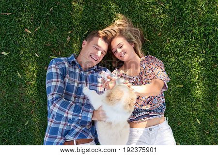 Loving couple smiling on grass overhead outdoors playing with their fluffy dog pet puppy