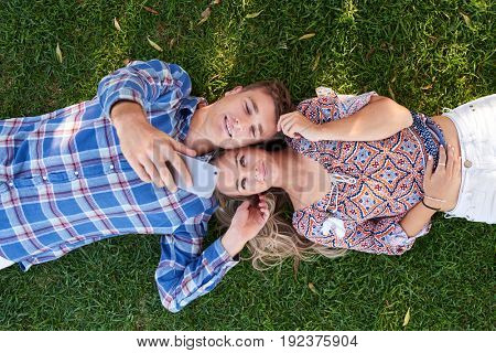 Cute couple smile for selfie lying down on green grass, overhead view loving affectionate moment