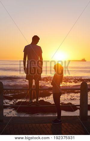 Silhouette of couple watching the sunset on the horizon, beautiful seaside scenary golden light sun flare