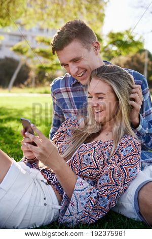 Young happy couple on date at park, laughing smiling at the phone cellphone smartphone