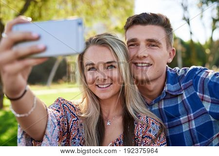 Happy couple in love using mobile phone smartphone to take selfie, smiling happy on date