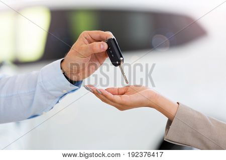 Car salesman handing car keys to woman in showroom