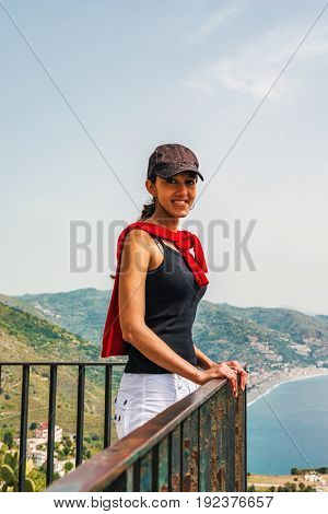 Smiling young woman on balcony by sea in city of Taorima, Sicily