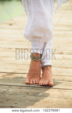 closeup of young woman barefoot legs in white clothes and anklets boho summer fashion style on wooden pontoone by the lake poster