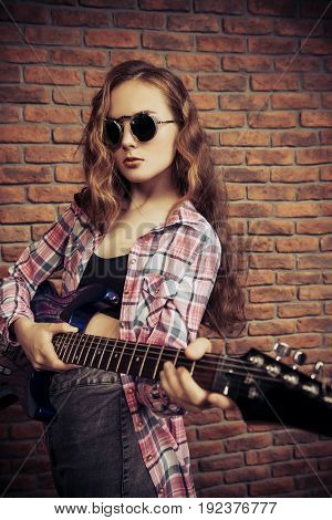 Portrait of an attractive girl with electric guitar. Rock music.