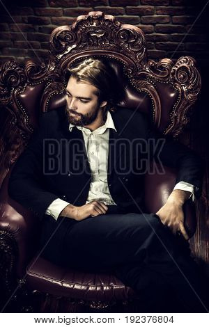 Portrait of a stylish handsome man on a vintage armchair. Fashion shot. Men's clothing and accessories.