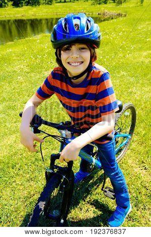 Cute cheerful boy is riding his bike. Happy summer holidays.