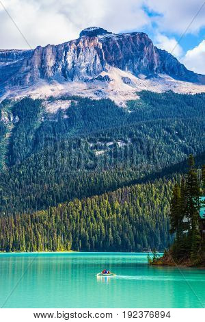 Emerald Lake in the Rocky Mountains of Canada. Group of tourists crosses the lake in a rowboat. The green lake surrounded by coniferous forest