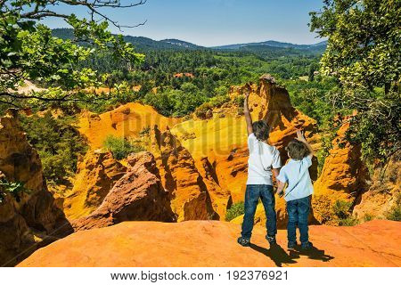 Orange and red picturesque hills in Languedoc. Two boys - brothers of seven and four years admire the magnificent nature