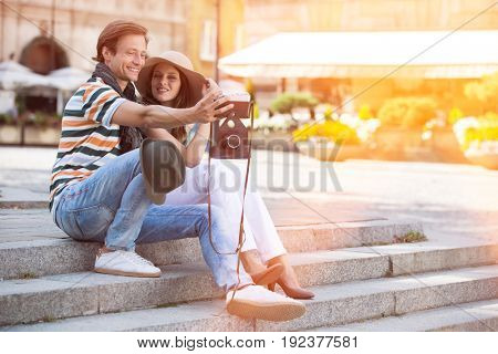 Tourist couple photographing on steps