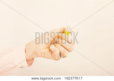 Businesswoman's hand holding cigarette lighter with flame in office