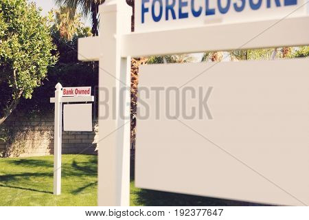 Foreclosure and Bank Owned signs in lawn