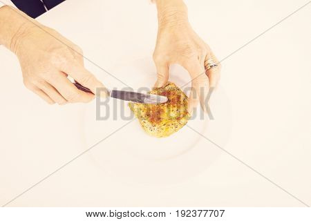 Businesswoman's hands spreading butter on bread