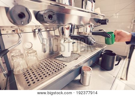 Close-up of coffee machine with hand holding cup
