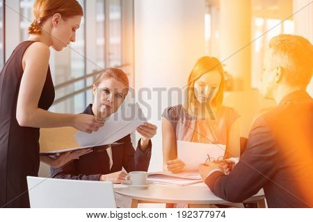 Business people doing paperwork in office cafeteria