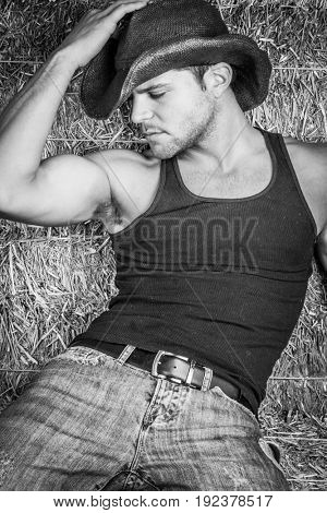 Country cowboy sitting in straw