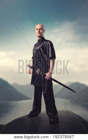 Wushu master with sword poses on top of mountain