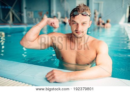 Athletic swimmer shows muscles, aqua sports