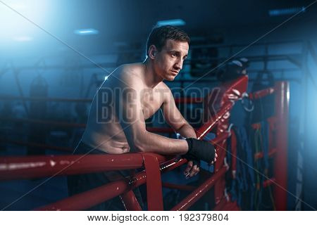 Boxer in black handwraps poses on ring ropes