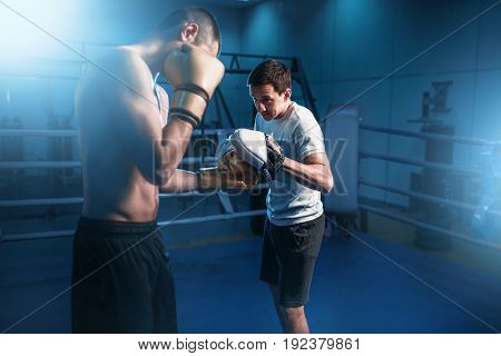Boxer in gloves exercises with personal trainer