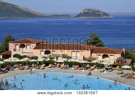 COLONNA BEACH RESORT, ARANCI GULF-SARDINIA ITALY. JUNE 12, 2017. People enjoy the beach in swimming pool and beach.