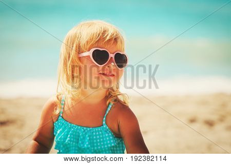 sun protection - little girl with suncream on tropical beach